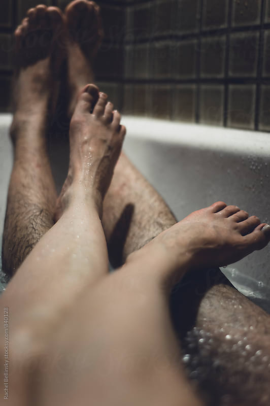 The legs and feet of a man and woman sharing a bath by Rachel Bellinsky for Stocksy United