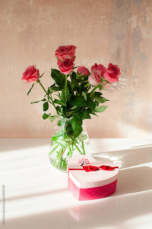 Bouquet of roses and a Valentine present on a white table  by Marija Mandic for Stocksy United