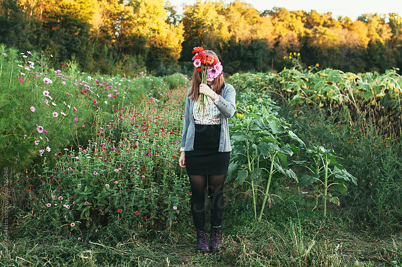 teen girl hides behind bouquet of fresh picked flowers by Deirdre Malfatto for Stocksy United