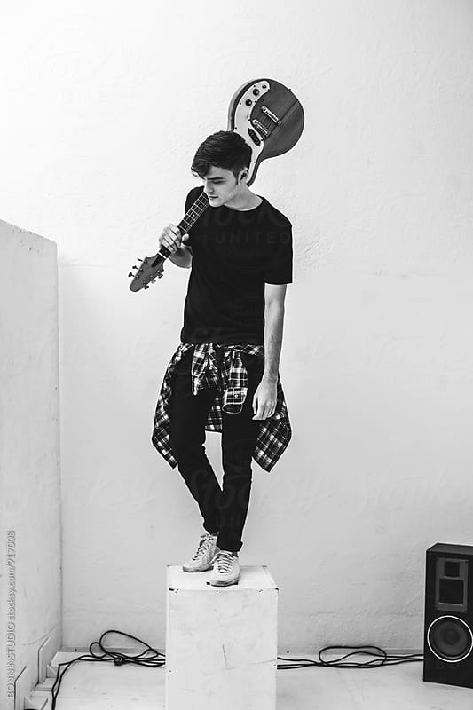 Young rocker holding his electric guitar in recording studio. by BONNINSTUDIO for Stocksy United