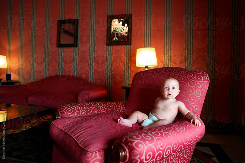 Baby Girl in Big Chair by Stephen Morris for Stocksy United
