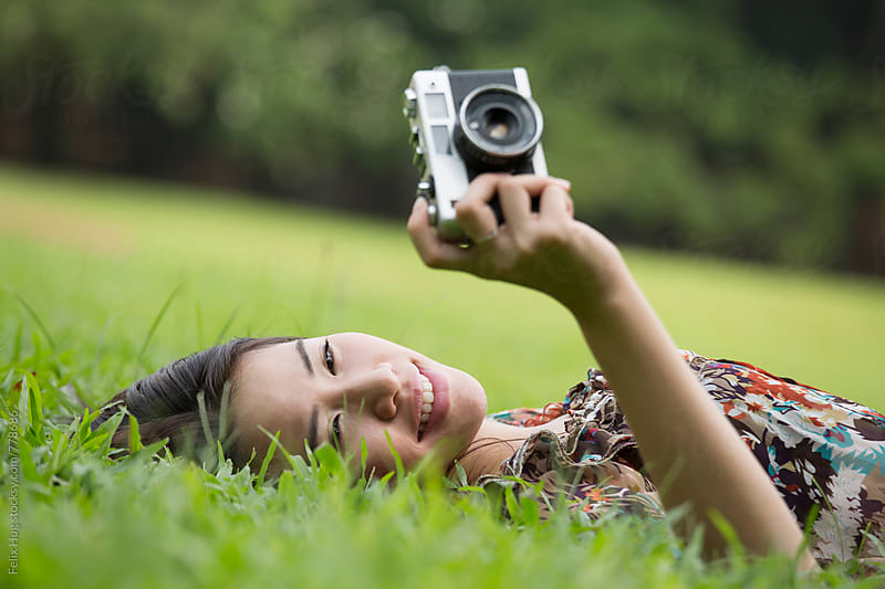 Woman with Camera in the grass by Felix Hug for Stocksy United