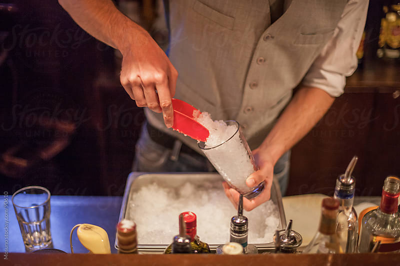 Bartender making a cocktail. by Mosuno for Stocksy United