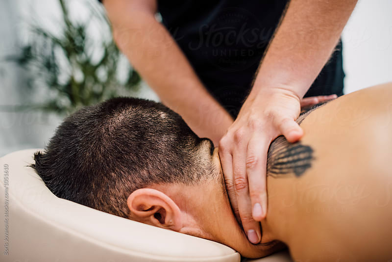 Man enjoying massage treatment indoor by Boris Jovanovic for Stocksy United
