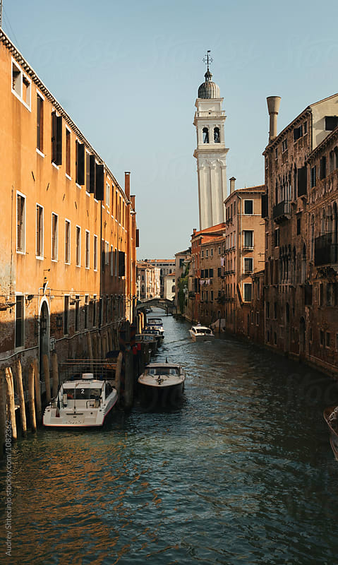 City of Venice/Canal with boats and houses with white bell tower of Church of St Mary by Audrey Shtecinjo for Stocksy United