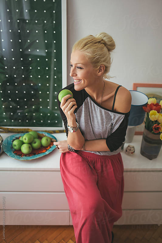 Woman Eating a Green Apple by Lumina for Stocksy United