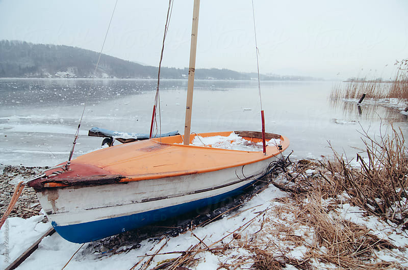 Small boat at the frozen lake Wallersee landscape in austria in winter by Robert Kohlhuber for Stocksy United