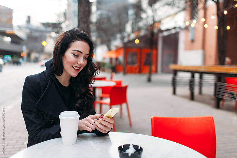 Young Woman Drinking Coffee with her Cellphone at a Cafe by Kayla Snell for Stocksy United