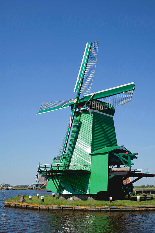 A classic green Dutch windmill surrounded by water under a clear blue sky by Ivo de Bruijn for Stocksy United
