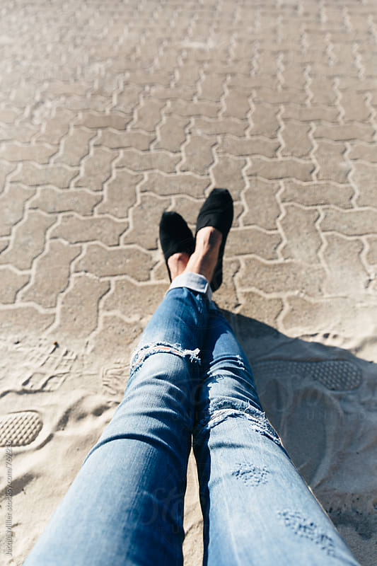 Looking down on legs of casual woman outdoors, wearing blue denim jeans and black shoes by Jacqui Miller for Stocksy United
