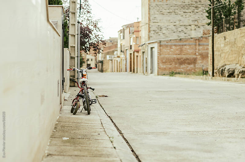 Two little bicycles parked by a wall by Eva Plevier for Stocksy United