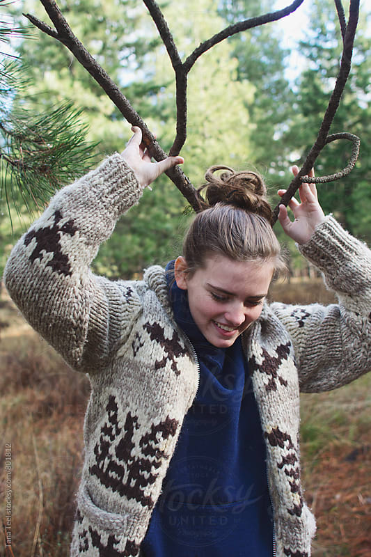 young woman holds branches up like antlers by Tana Teel for Stocksy United