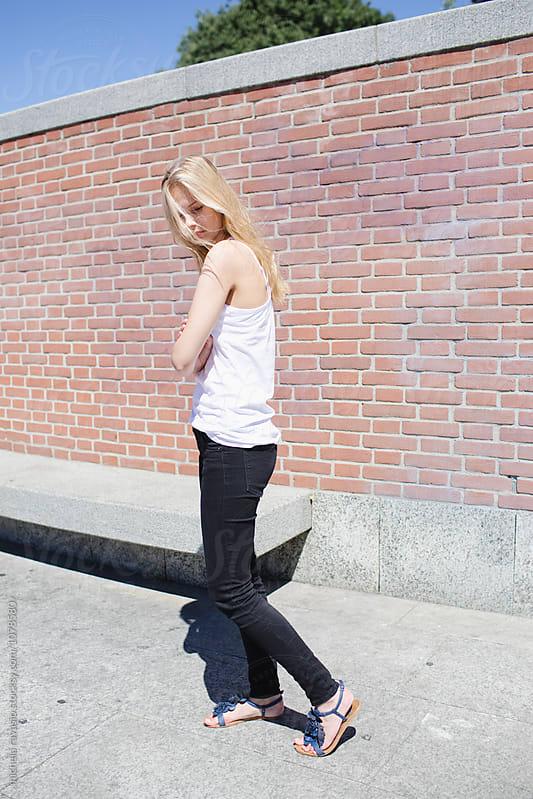 Girl walking near a brick wall by michela ravasio for Stocksy United