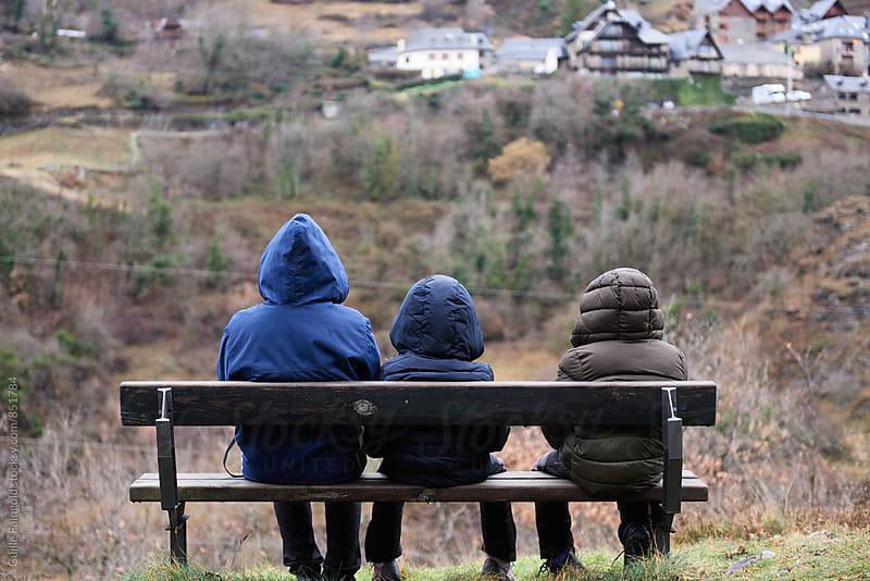 Back view of three people sitting on bench in countryside by Guille Faingold for Stocksy United