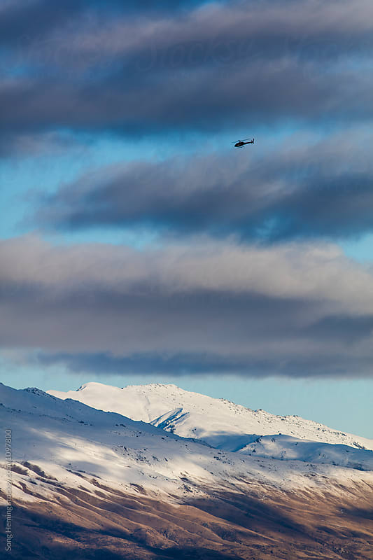 Helicopter overflying in the snow mountains by Song Heming for Stocksy United