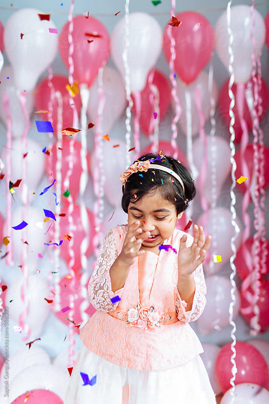 Cute little girl celebrating with confetti at her birthday party by Saptak Ganguly for Stocksy United