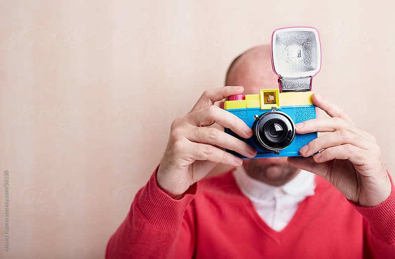 photographer holding toy plastic camera with flash by Alexey Kuzma for Stocksy United