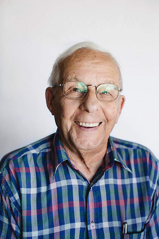 Happy senior man looking at camera on white background by Rob and Julia Campbell for Stocksy United