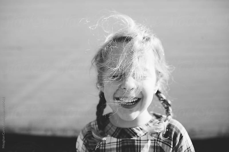 portrait of a little girl with a big smile as her hair blows in the wind by Meaghan Curry for Stocksy United