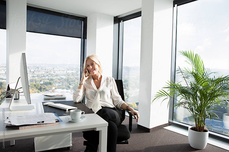 Businesswoman Telephoning at Her Office by Lumina for Stocksy United