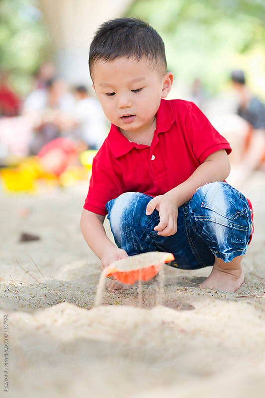 Child playing sand with toy tools at beach by Lawren Lu for Stocksy United
