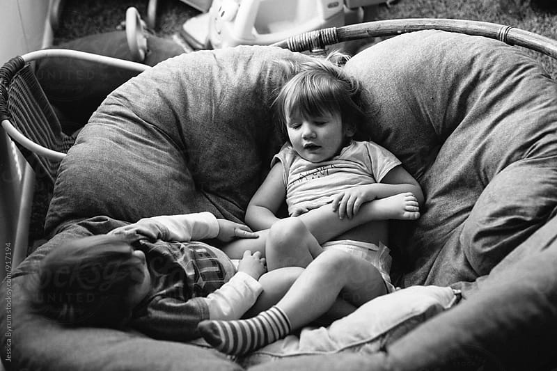 Black and white image of young Irish twin siblings sleeping in a papasan chair.  by Jessica Byrum for Stocksy United