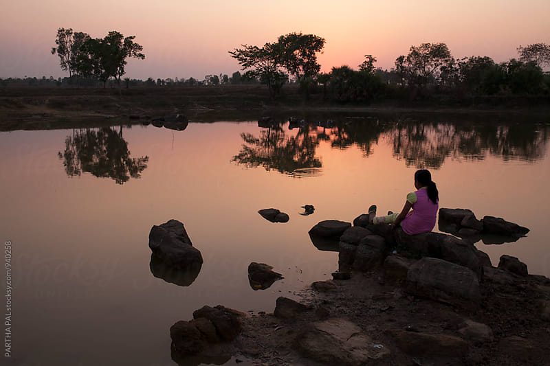 A girl sitting in front of a waterbody and enjoying sunset by PARTHA PAL for Stocksy United