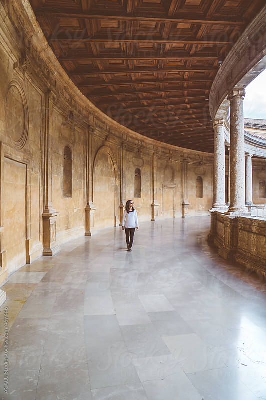 Tourist visiting a palace with columns by ACALU Studio for Stocksy United
