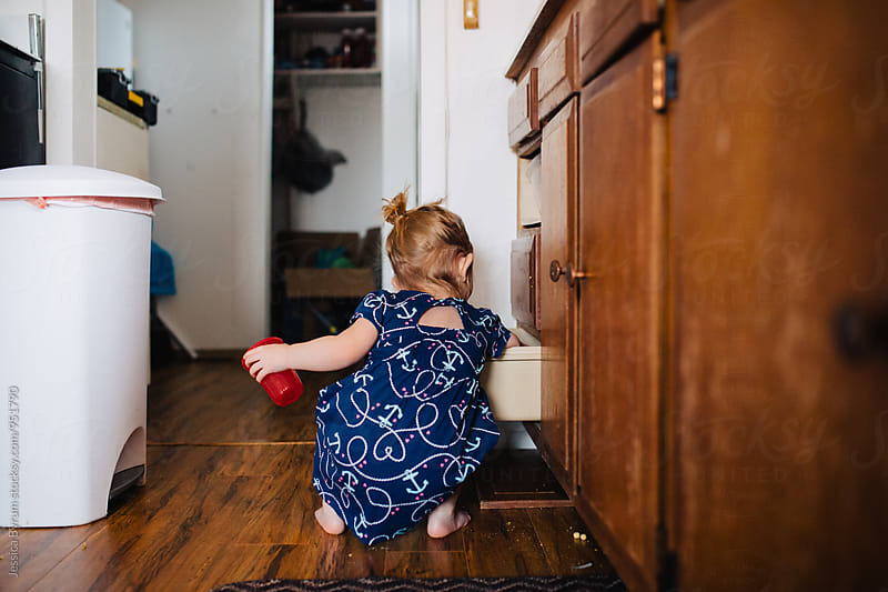 Toddler girl getting into kitchen drawer by Jessica Byrum for Stocksy United