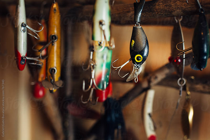 Colorful fishing tackles hanging on a wall by Gabriel (Gabi) Bucataru for Stocksy United