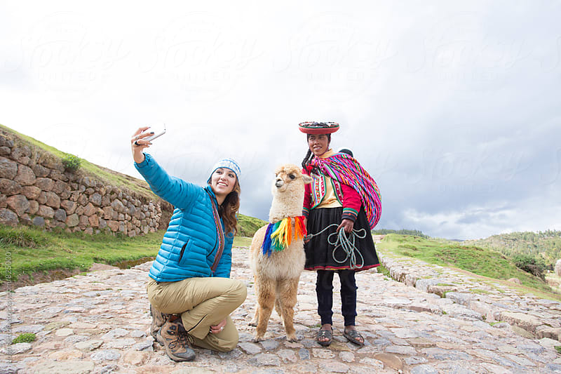 Female Tourist with traditional Peruvian women. Peru. by Hugh Sitton for Stocksy United