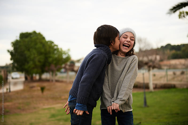 Boy kissing laughing little girl by Guille Faingold for Stocksy United