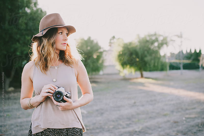 pretty woman holding camera with hat on in a field by Kristin Rogers Photography for Stocksy United
