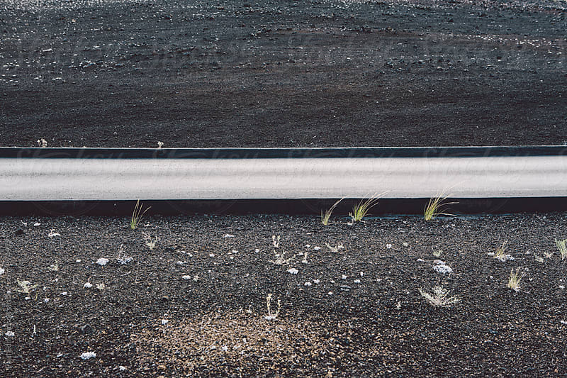 Detail of paved road through sparse volcanic landscape by Paul Edmondson for Stocksy United