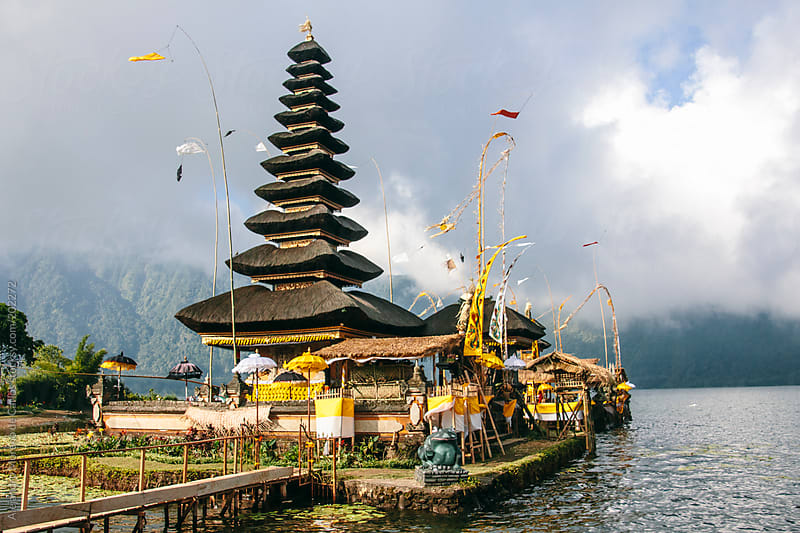 Asian temple and flags on a lake in Bali, Indonesia by Alejandro Moreno de Carlos for Stocksy United