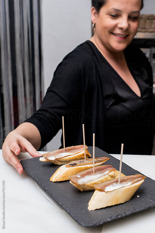 Woman placing a dish of anchovies in a tapas bar by Bisual Studio for Stocksy United