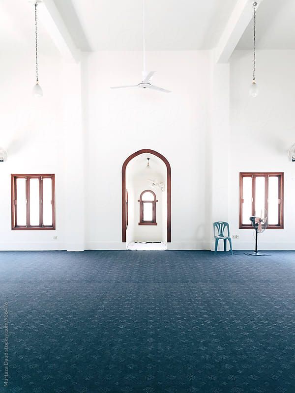 A  mosque with white walls and  blue carpet by Murtaza Daud for Stocksy United