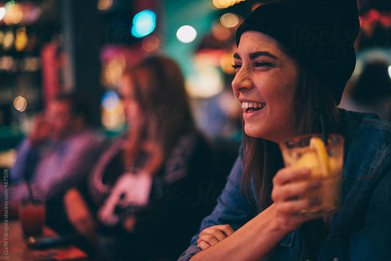 Young girl smiling in a pub by Guille Faingold for Stocksy United