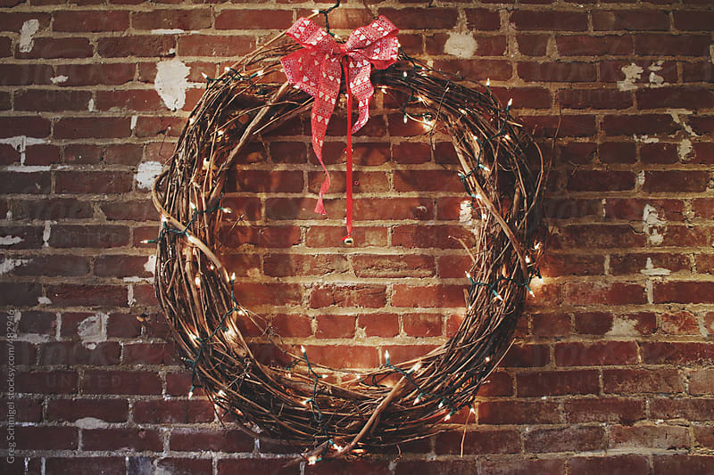 Christmas holiday wreath with a red bow and festive white lights by Greg Schmigel for Stocksy United