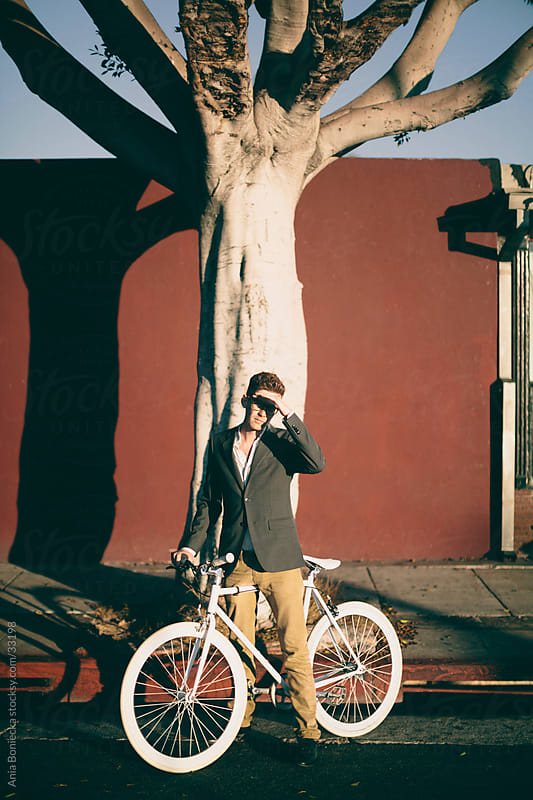 A handsome man riding his bike on a city street by Ania Boniecka for Stocksy United