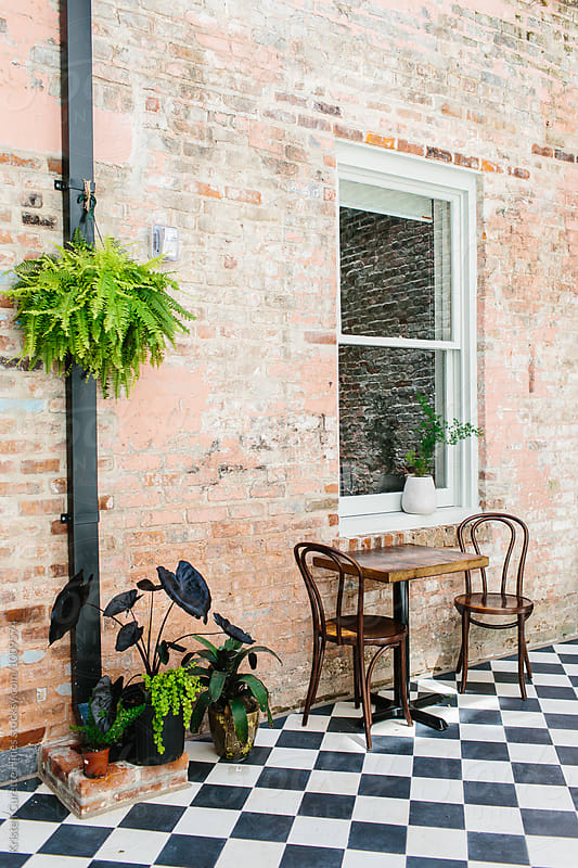 A lounge area with seating / checkered floor & vintage brick walls.  by Kristen Curette Hines for Stocksy United