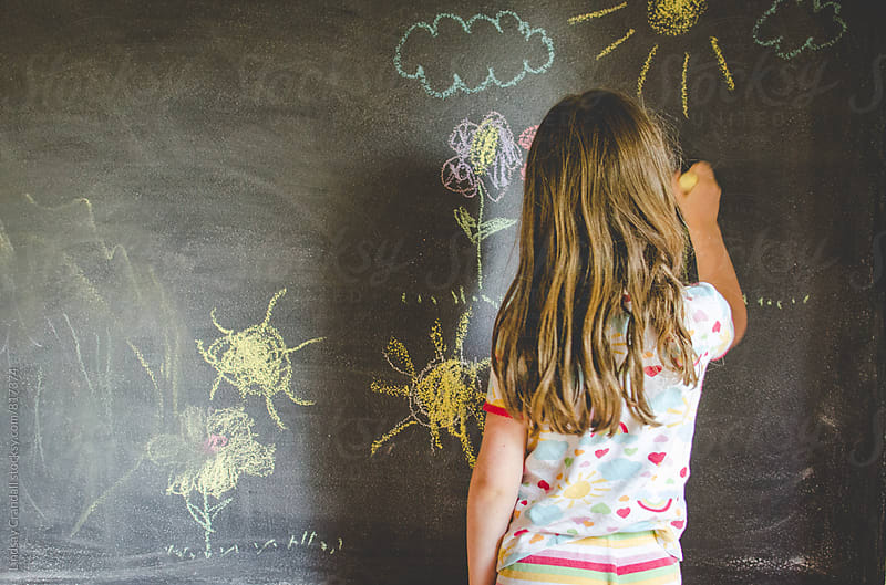 Child drawing on chalkboard by Lindsay Crandall for Stocksy United