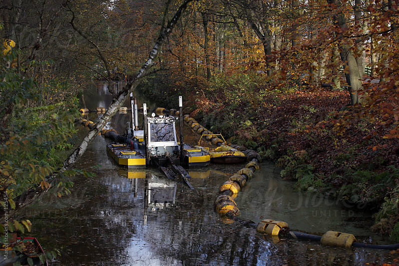 Dredge machine pumping mud out of a waterway by Marcel for Stocksy United