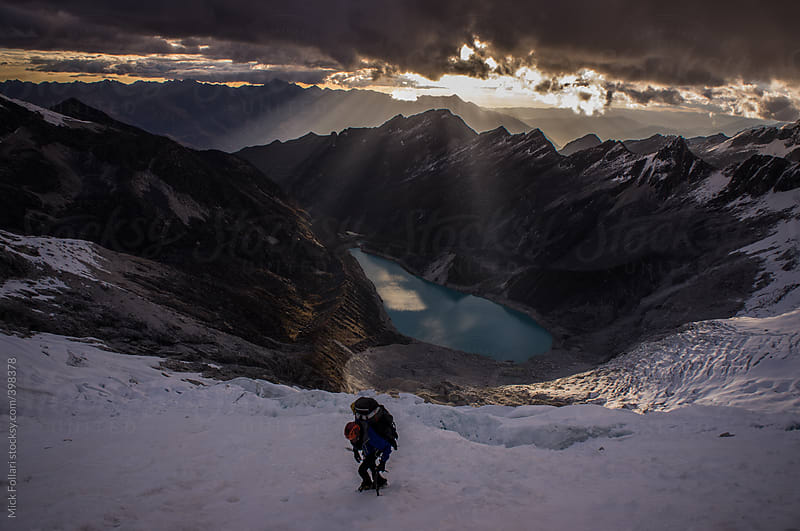Mountain climber on glacier with sunset rays behind by Mick Follari for Stocksy United
