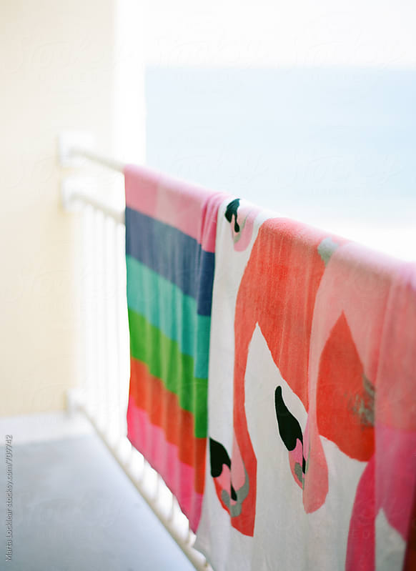 Colorful towels drying on a railing by Marta Locklear for Stocksy United