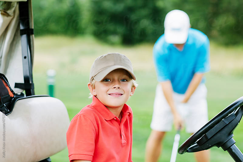 smiling boy golfing with his father by Kelly Knox for Stocksy United