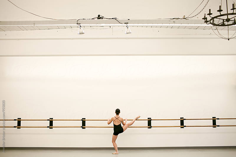 A woman stretches her legs in a dance studio by Jen Brister for Stocksy United