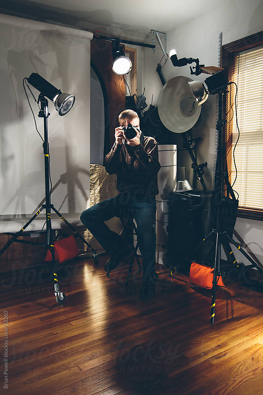 portrait photographer in studio with lighting gear by Brian Powell for Stocksy United