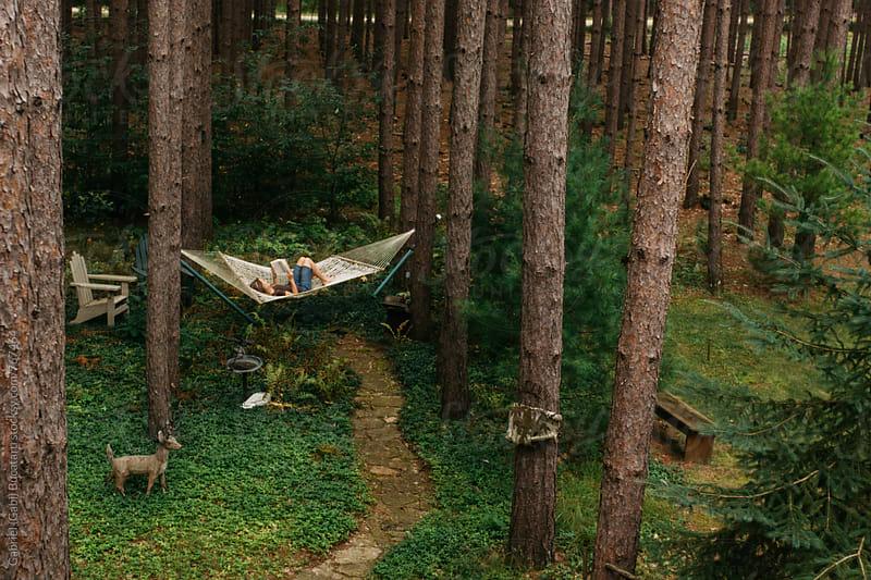 Woman in a hammock in a forest, reading by Gabriel (Gabi) Bucataru for Stocksy United