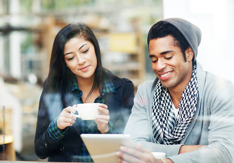 Two people looking over tablet in coffee shop by Isaac Lane Koval for Stocksy United